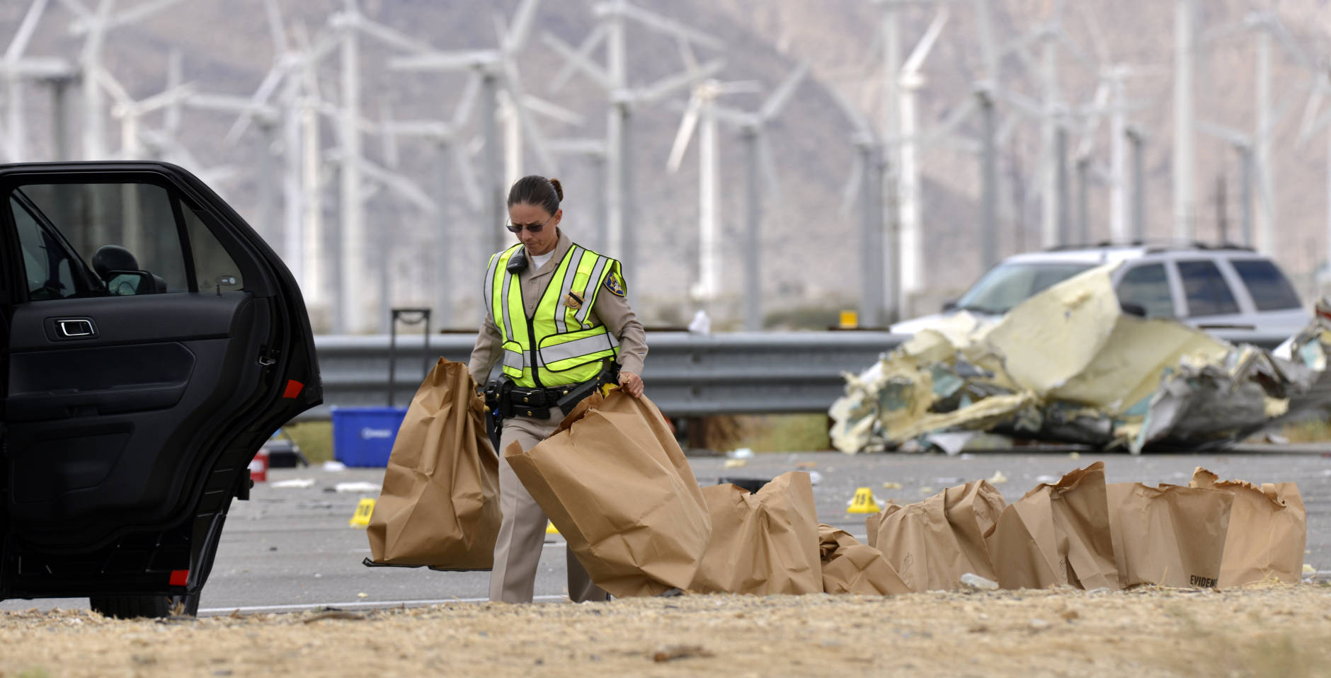A California Highway Patrol officer load items in bags into a CHP vehicle after a tour bus crashed with a semi-truck on Interstate 10, west of the Indian Canyon Drive off-ramp, in Desert Hot Springs, near Palm Springs, Calif., Sunday, Oct. 23, 2016. The tour bus and the semi-truck crashed on the highway in Southern California early Sunday, killing at least a dozen of people and injuring at least 30 others, some critically, the California Highway Patrol said. (AP Photo/Rodrigo Pena)