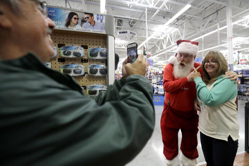 In this file photo, a man playing the role of Santa Claus, center, and Karyn Ochiuzzo, right, of Wood-Ridge, N.J., pose for a photo taken by Bill Ochiuzzo at Wal-Mart in Teterboro, N.J. Wal-Mart may be known for its every day low prices but this holiday season it wants to be known for service too, Wednesday, Oct. 26, 2016   AP  photo by Julio Cortez, St. George News