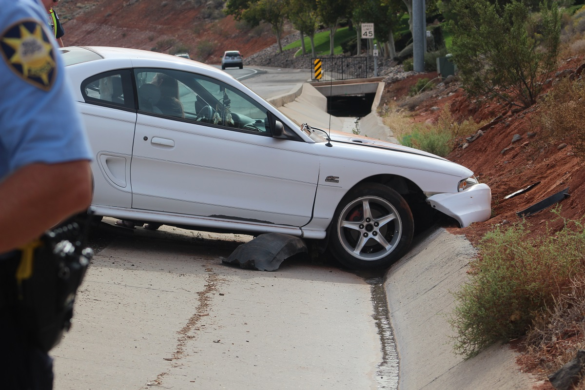 White Ford Mustang sustained extensive damage after the driver lost control of the car that went through four lanes of traffic before hitting the embankment on Bluff Street Thursday, St. George, Utah, Oct. 27, 2016 | Photo by Cody Blowers, St. George News