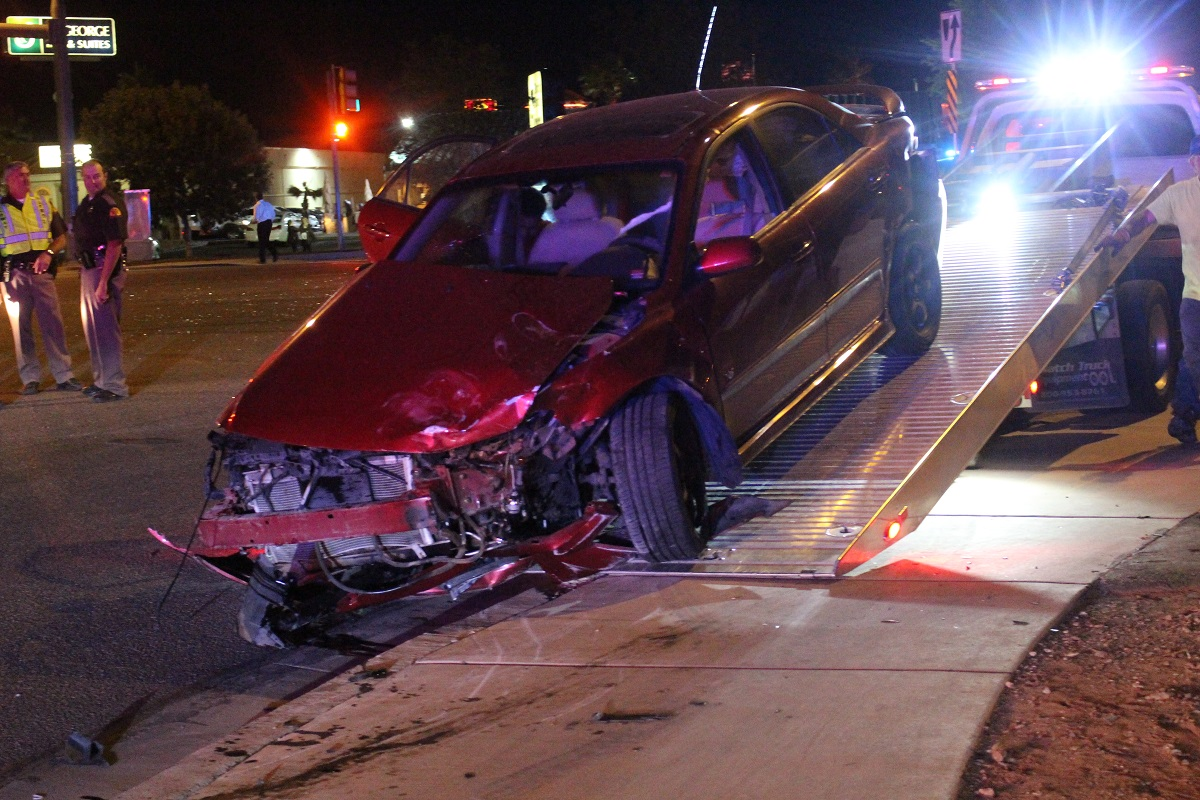 Red Mazda four-door incurred extensive damage in two-vehicle crash in the intersection of Bluff Street and Blackridge Drive on a busy Saturday night, St. George, Utah, Oct. 15, 2016 | Photo by Cody Blowers, St. George News