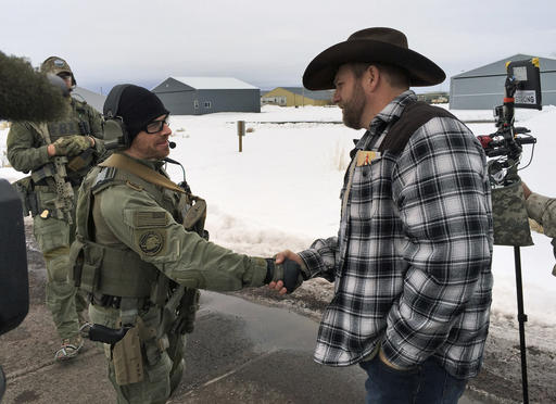 FILE - In this file photo, Ammon Bundy, right, shakes hand with a federal agent guarding the gate at the Burns Municipal Airport in Burns, Ore. The stunning acquittal of seven people who occupied a federal bird refuge in Oregon as part of a Western land dispute was a rejection of the prosecution's conspiracy case, not an endorsement of the armed protest, a juror said Friday. Burns, Oregon, Jan 22, 2016 | File photo by Keith Ridler (AP), St. George News