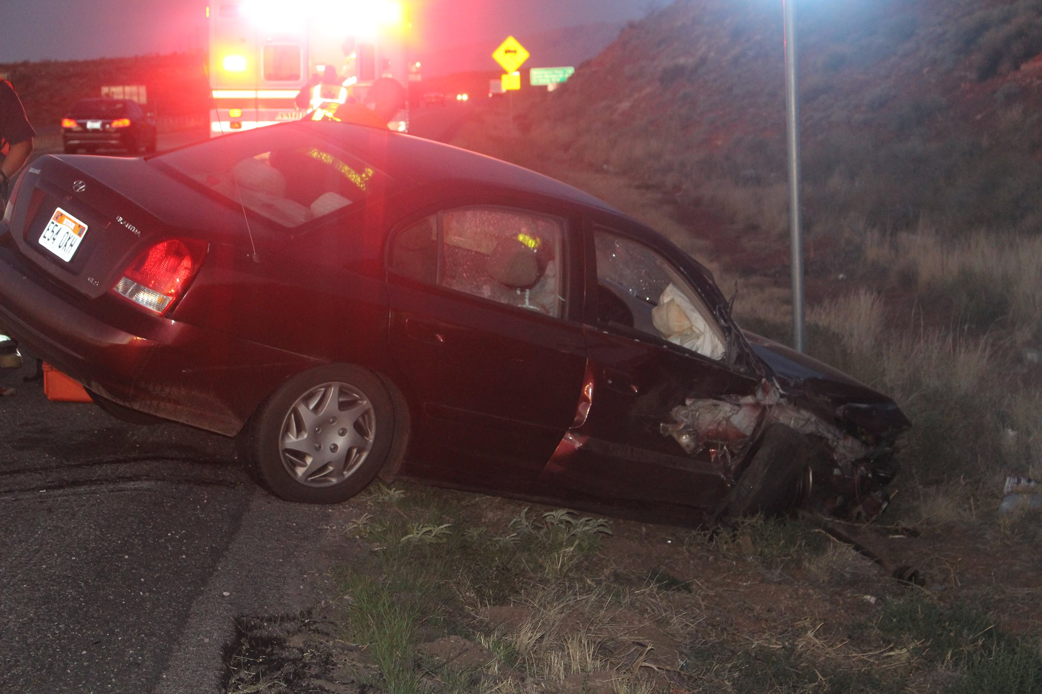 A red Hyundai sits node down into the ditch next to I-15 by the Hurricane exit after a wreck involving a parked minivan. Washington, Utah, October 15, 2016 | Photo by Ric Wayman, St. George News