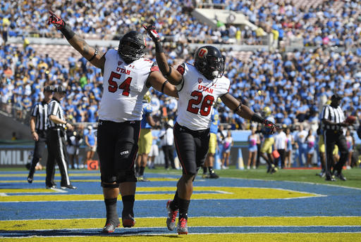 Utah running back Joe Williams, right, celebrates his touchdown with offensive lineman Isaac Asiata during the first half of an NCAA college football game against UCLA, Saturday, Oct. 22, 2016, in Pasadena, Calif. (AP Photo/Mark J. Terrill)