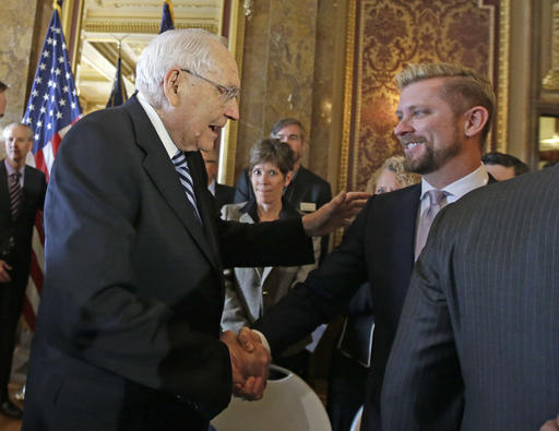 "FILE -  Elder L. Tom Perry, left, of the Church of Jesus Christ of Latter-day Saints Quorum of the Twelve Apostles shakes hands with Equality Utah executive director Troy Williams after Utah lawmakers introduced a landmark anti-discrimination bill during a news conference at the Utah State Capitol. Mormon leaders are telling gay and lesbian church members that attraction to people of the same sex is not a sin or a measure of their faithfulness. But they are reminding those members that acting on those feelings by having sex violates fundamental doctrinal beliefs that won't change. The message is part of the Mormon church's ""Mormon and Gay"" website launched Tuesday, Oct. 25, 2016, with dozens of articles, teachings, videos and stories from Mormons who identify themselves as gay. Salt Lake City, Utah, March 4, 2015 