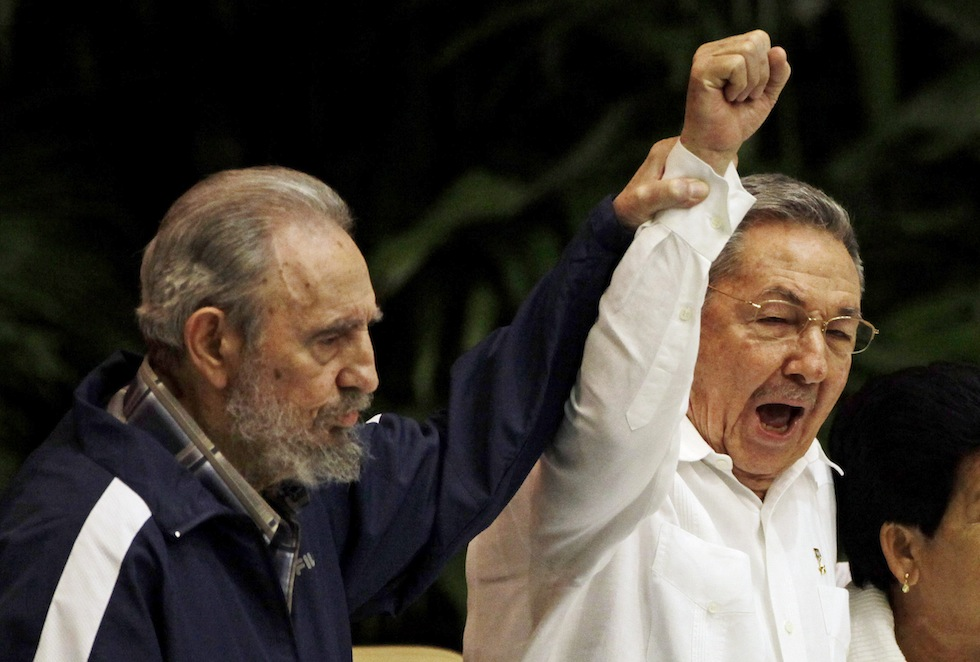 FIn this April 19, 2011 file photo, Fidel Castro, left, raises his brother's hand, Cuba's President Raul Castro, center, as they sing the anthem of international socialism during the 6th Communist Party Congress in Havana, Cuba. Cuban President Raul Castro has announced the death of his brother Fidel Castro at age 90 on Cuban state media on Friday, Nov. 25, 2016. | AP Photo/Javier Galeano, File, St. George News