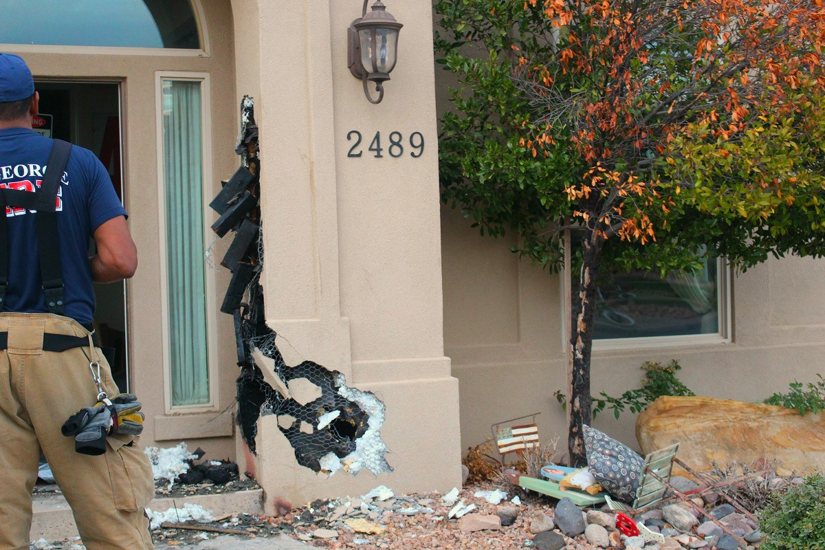 Fire crews broke through the column and adjacent wall where a fire broke out at a residence on 2830 South Street Wednesday, St. George, Utah, Nov. 30, 2016 | Photo by Cody Blowers, St. George News.