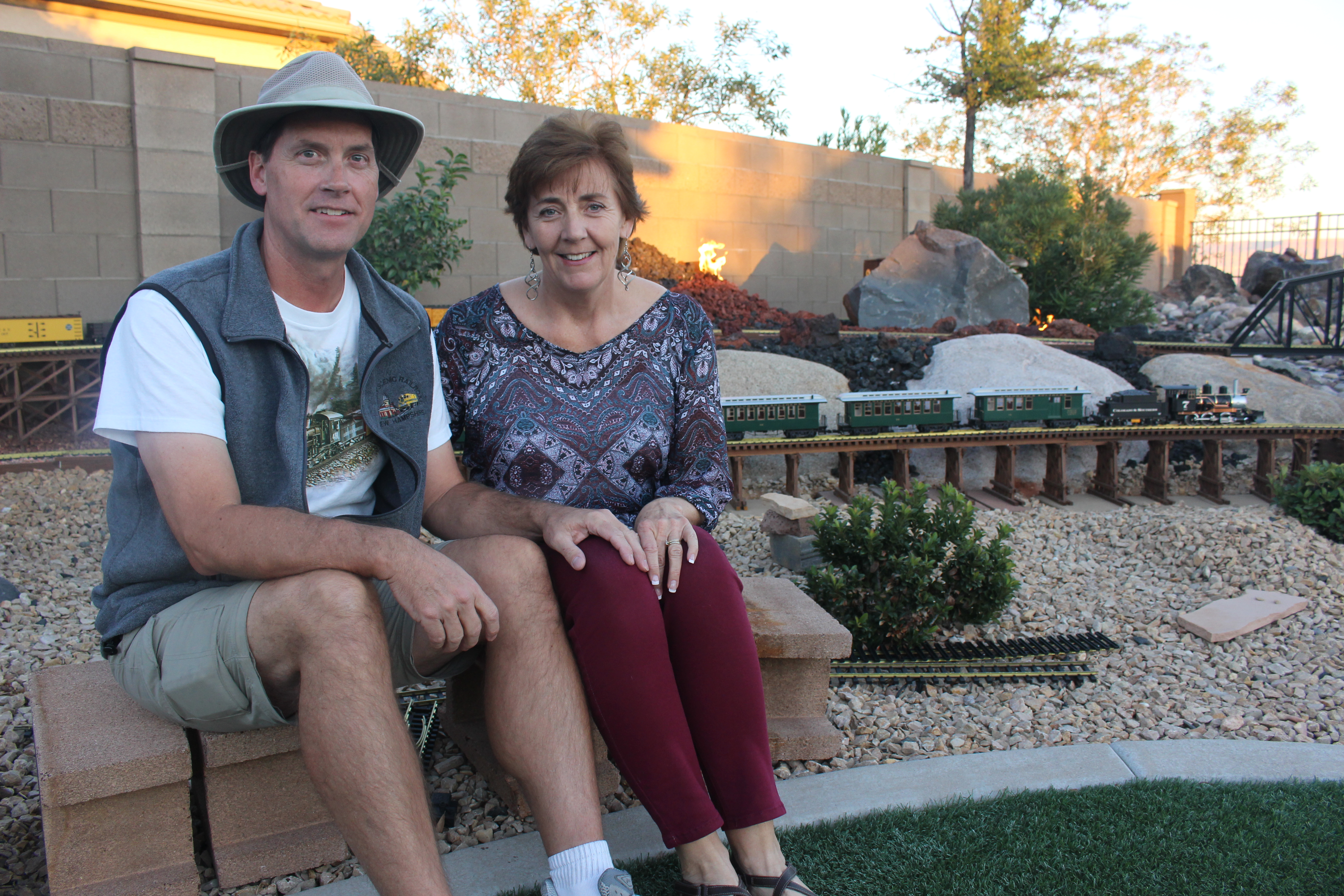 Tim Fitch and his wife pose for a photo near the garden scale model railroad in their backyard, Washington City, Utah, Nov. 11, 2016 | Photo by Joseph Witham, St. George News