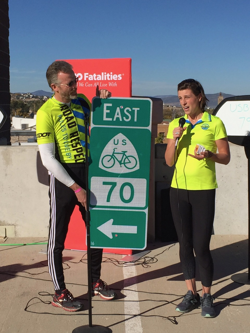"L-R: Utah Department of Transportation engineer and Southern Utah Bicycle Alliance board member Nathan Merrill; UDOT Active Transportation planner Heidi Goedhart displaying the final U.S. Bicycle Route sign to be installed in Utah at a ""golden bolts"" ceremony in Cedar City, Utah, Oct. 26, 2016 