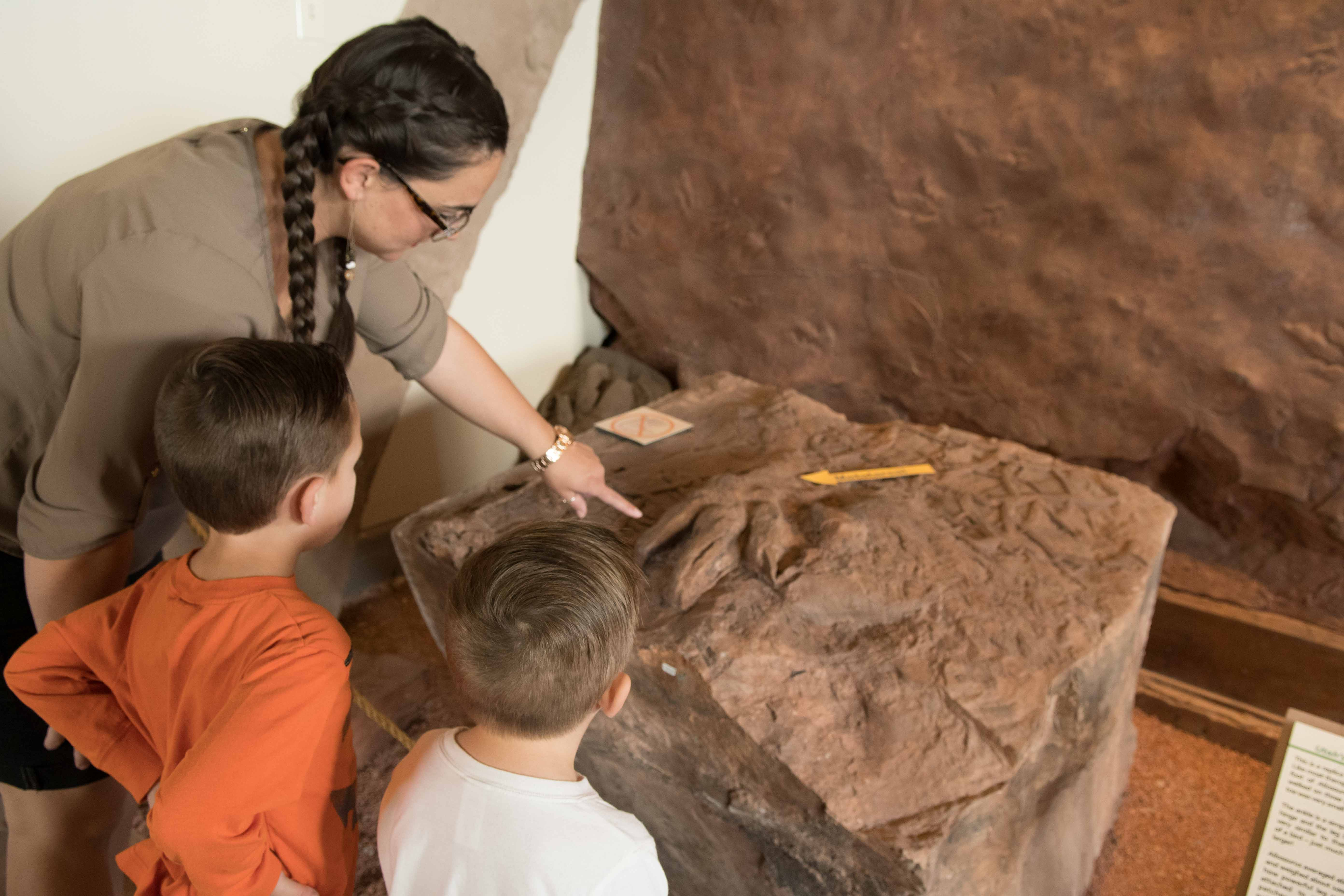 Kimber Bringhurst and boys inspect dinosaur natural tracks casting, Dinosaur Discovery Site, St. George, Utah, Oct. 31, 2016 | Photo by and courtesy of Jim Lillywhite, St. George News