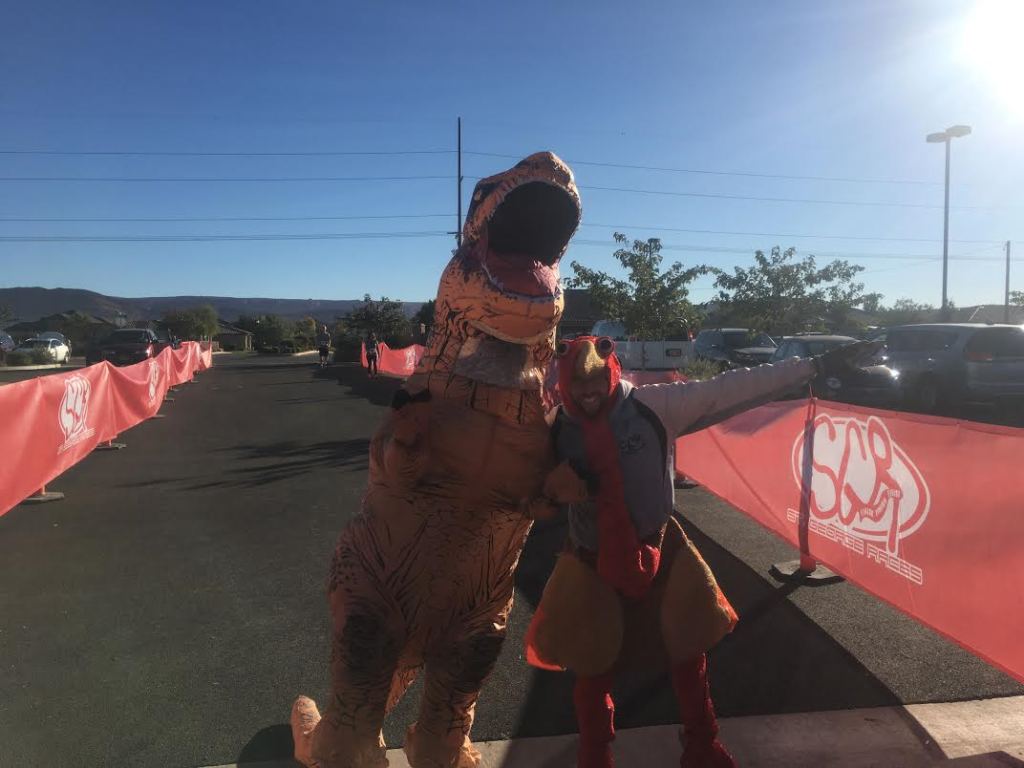 L-R: Matthew Ferreira as T. Rex and Aaron Metler as a turkey pose for a photo before the start of the Turkey Trot 5K and Fun Run at Hela Seegmiller Historic Farm, St. George, Utah, Nov. 19, 2016 | Photo by Hollie Reina, St. George News