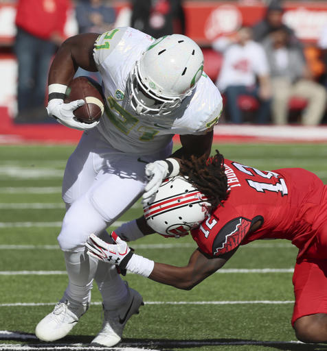 Oregon running back Royce Freeman, (21), runs out of a tackle by Utah defensive back Justin Thomas, (12), in the first half during an NCAA college football game, Saturday, Nov. 19, 2016, in Salt Lake City. (AP Photo/George Frey)