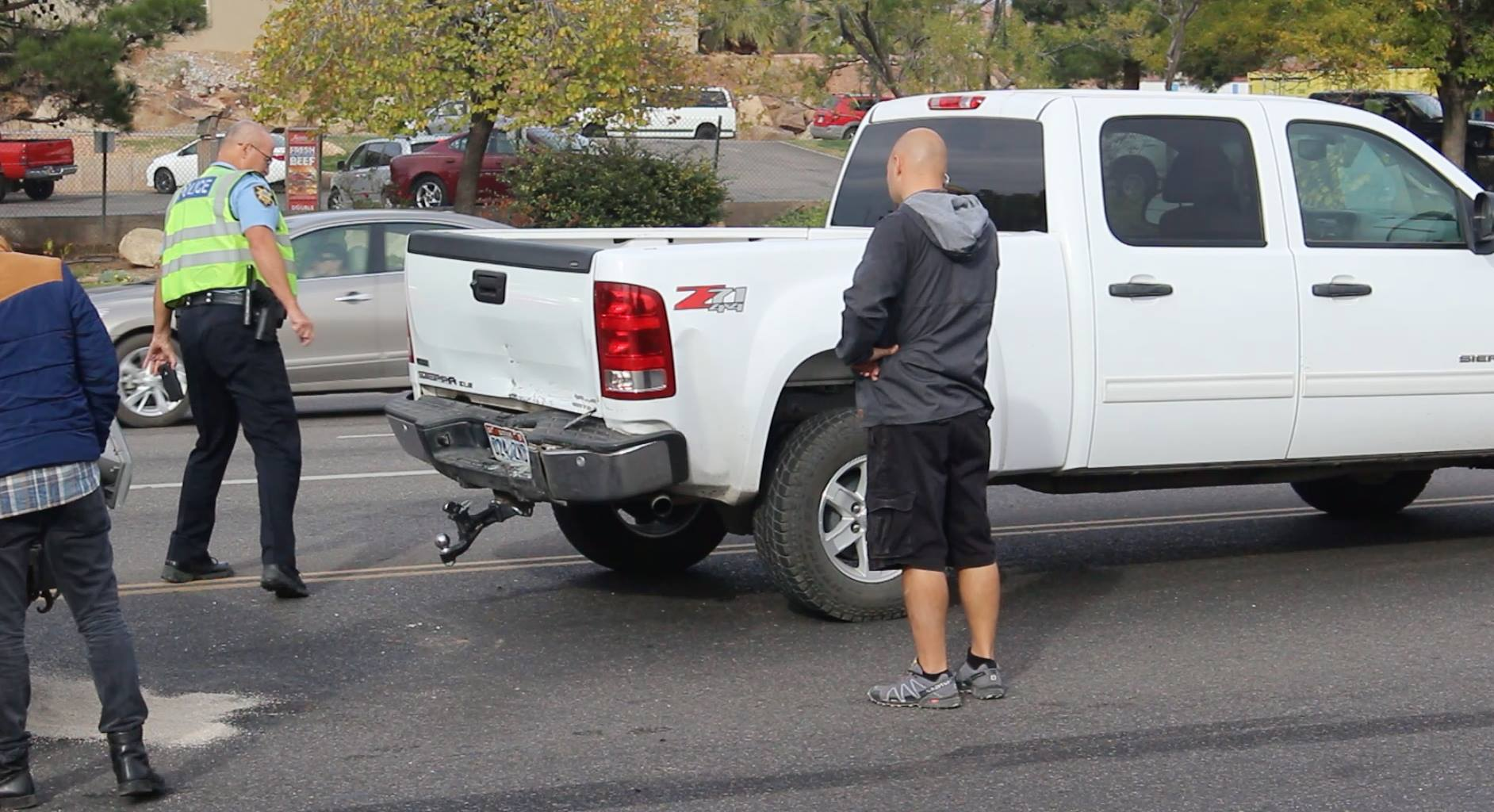 St. George Police Officer Jamison Hale and the truck owner inspect a GMC pickup involved in a crash Wednesday, St. George, Utah, Nov. 16, 2016 | Photo by Mike Cole, St. George News