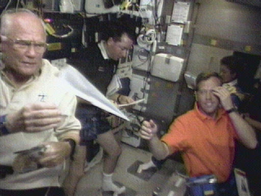 FILE - In this Sunday, Nov. 1, 1998 image made from video, astronaut John Glenn, left, retrieves a paper airplane for pilot Steven Lindsey, foreground right, in the space shuttle Discovery's middeck. Astronaut Stephen Robinson, background right, and Japanese astronaut Chiaki Mukai look over paper work in the background. Glenn died Thursday, Dec. 8, 2016, at the age of 95. (AP Photo/NASA, File)