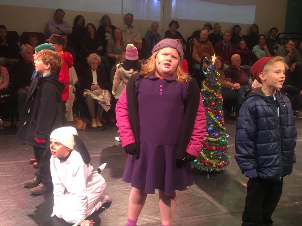 "Erika Wright (in purple) as Violet joins the cast of St. George Musical Theater's production of ""A Charlie Brown Christmas"" in singing Christmas carols at the St. George Opera House, St. George, Utah, Dec. 3, 2016 