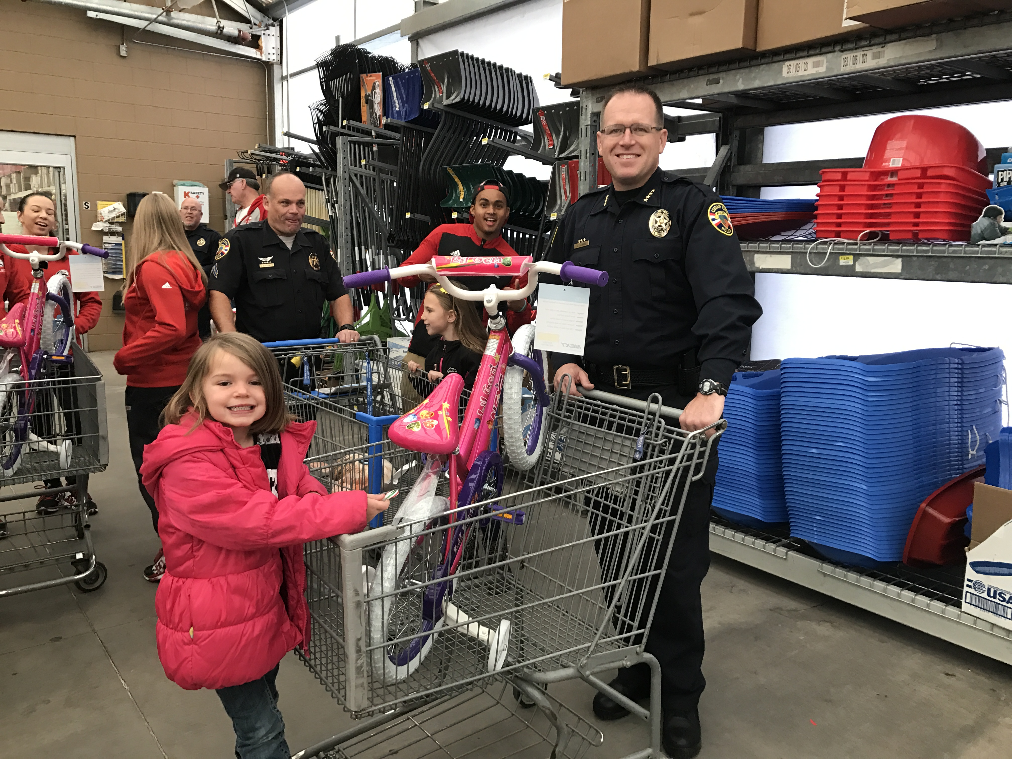 Cedar City Police Chief Darin Adams poses with the child he was paired with at the Shop with a Cop event. St. George, Utah, Dec. 10, 2016 | Photo by Tracie Sullivan, St. George / Cedar City News