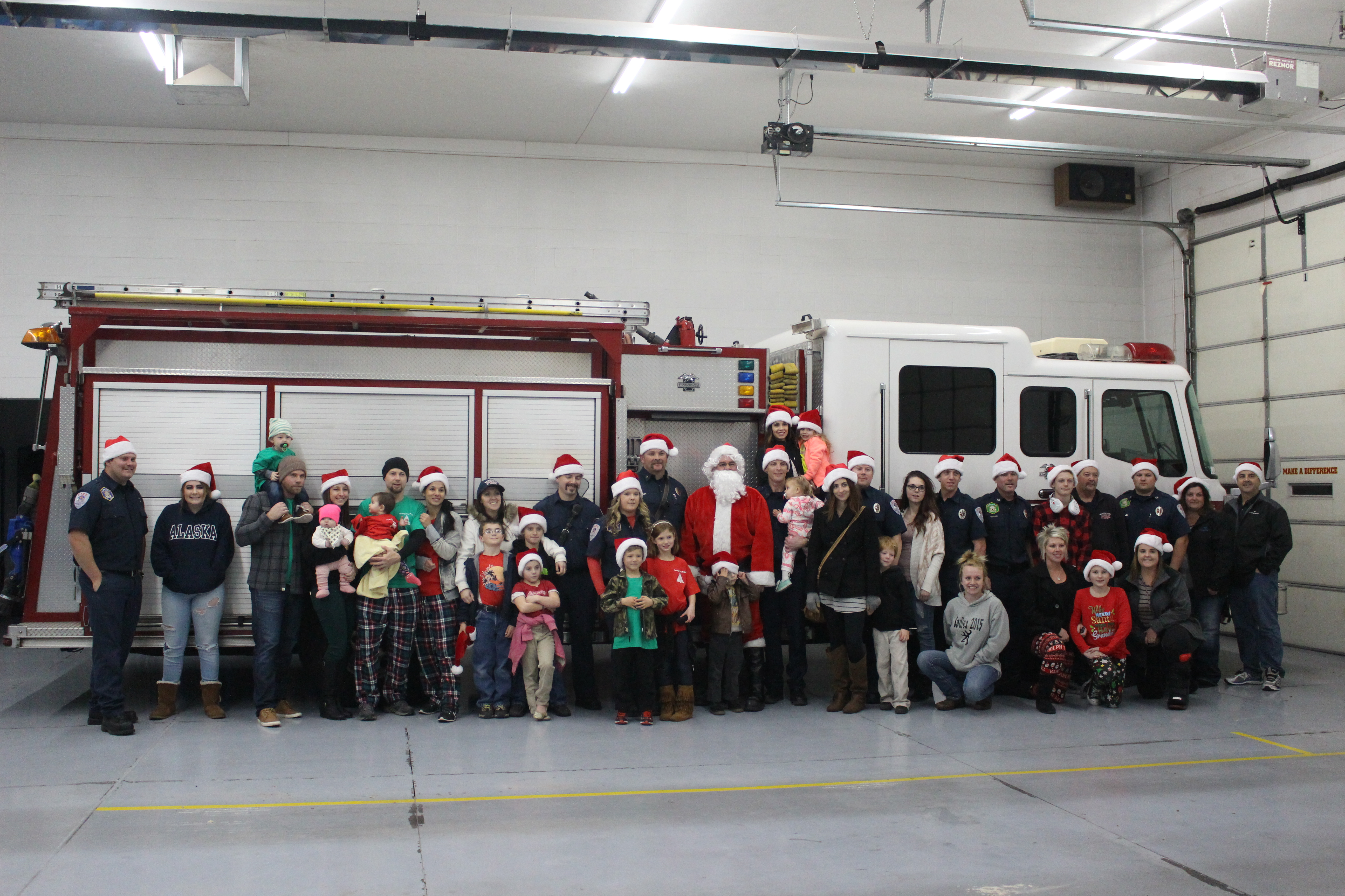 Washington City Fire personnel and their families pose next to a fire engine before delivering gifts for the Angel Tree Project, Washington, Utah, Dec. 22, 2016 | Photo by Joseph Witham, St. George News