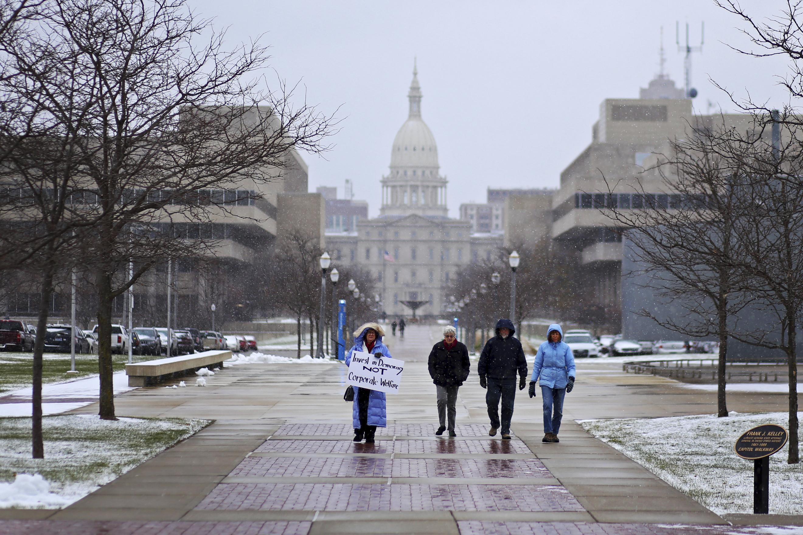 In this Dec. 8, 2016, AP photo, Michigan residents walk towards the Michigan State Supreme Court for a rally to speak out against the courts decision to shut down Michigan's recount on Thursday, in Lansing. Michigan's recount of presidential votes is over after a judge lifted an order that forced a statewide review of millions of ballots. The recount lasted three days in more than 20 of the state's 83 counties. Lansing, Michigan, Dec. 8, 2016 | Photo by Samantha Madar /Jackson Citizen Patriot via AP; St. George News