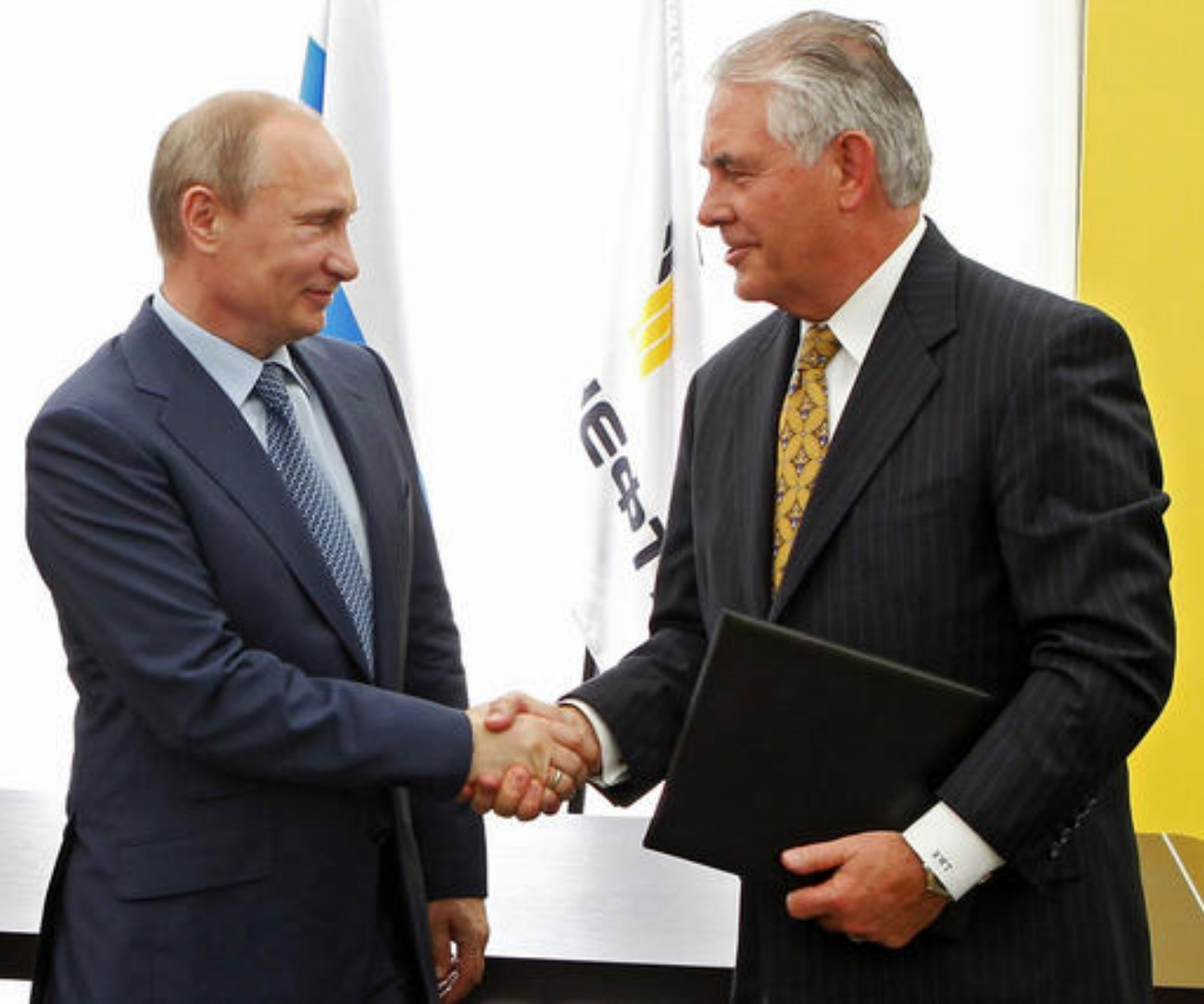 File photo from 2012: Russian President Vladimir Putin, left, and ExxonMobil CEO Rex Tillerson shake hands at a signing ceremony of an agreement between state-controlled Russian oil company Rosneft and ExxonMobil at the Black Sea port of Tuapse, southern Russia. President-elect Donald Trump selected Tillerson to lead the State Department on Monday, Dec. 12, 2016. Photo originally taken in Moscow, Russia, June 12, 2012 | Photo by Mikhail Klimentyev/RIA-Novosti, Presidential Press Service via AP, Pool