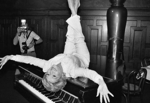 "FILE- In this Sept. 8, 1982, file photo, actress Debbie Reynolds poses on a grand piano at a New York restaurant, as she promotes the revival of the hit musical ""The Unsinkable Molly Brown."" Reynolds, star of the 1952 classic ""Singin' in the Rain"" died Wednesday, Dec. 28, 2016, according to her son Todd Fisher. She was 84. (AP Photo/Marty Lederhandler, File)"