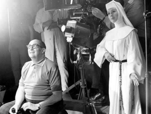 "FILE- In this Nov. 15, 1965, file photo, Debbie Reynolds, dressed as nun for her role as a singing nun in the MGM picture of that name, practices her next scene while she watches a scene being filmed. Reynolds, star of the 1952 classic ""Singin' in the Rain"" died Wednesday, Dec. 28, 2016, according to her son Todd Fisher. She was 84.(AP Photo, File)"
