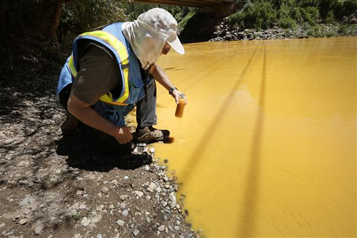 FILE - In this file photo, Dan Bender, with the La Plata County Sheriff's Office, takes a water sample from the Animas River near Durango, Colo., Thursday, Aug. 6, 2015. The U.S. Environmental Protection Agency said that a cleanup team was working with heavy equipment to secure an entrance to the Gold King Mine. Workers instead released an estimated 1 million gallons of mine waste into Cement Creek, which flows into the Animas River. (Jerry McBride/The Durango Herald via AP)