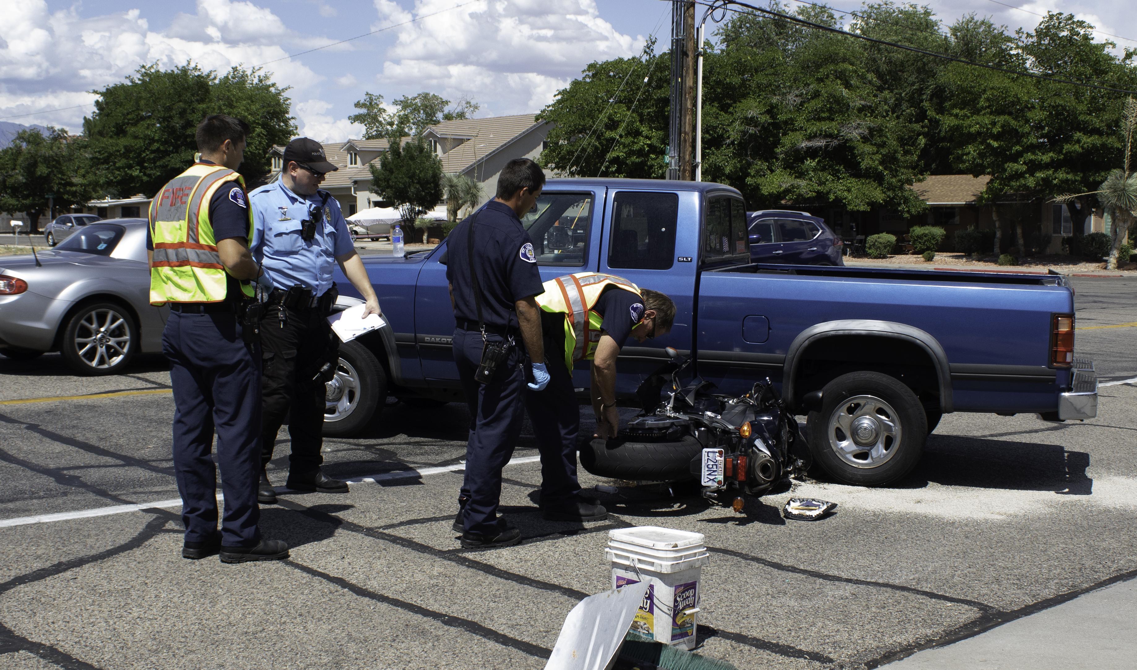 Motorcycle wedged under truck after crash near Bluff Street